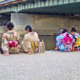 Girls sitting at river bank Kyoto