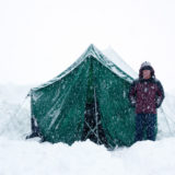 Girl standing next to tent in snow