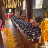 Buddhist monk with rows of bowls